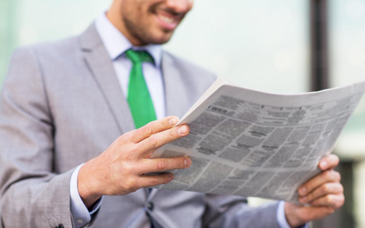 Mann mit Zeitung liest Nachrichten