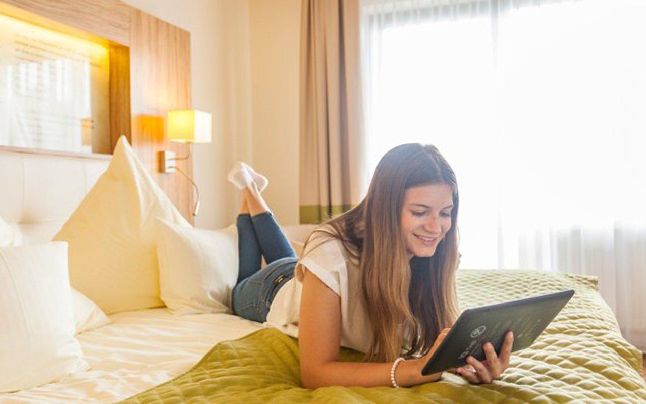 Gast auf dem Bett mit der digitalen Gästemappe iQ Tab