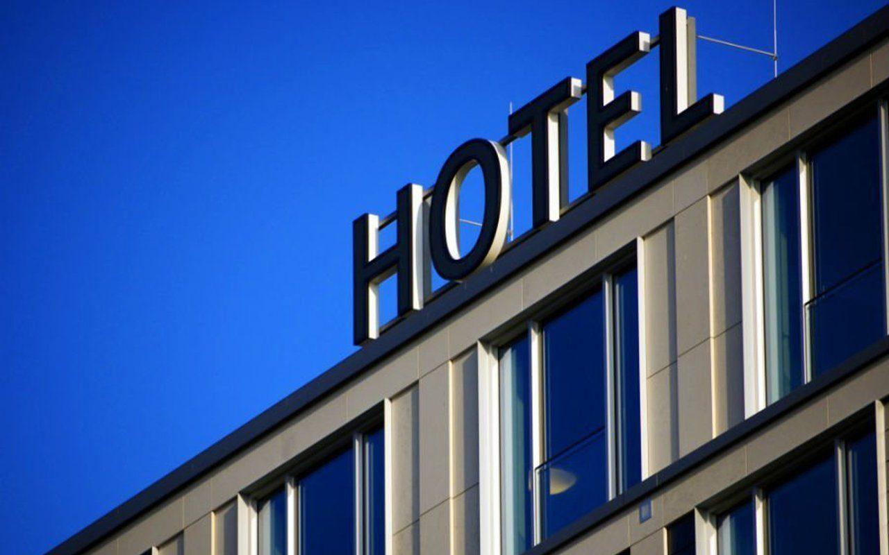 Fassade mit Schriftzug eines Hotels unter blauem Himmel