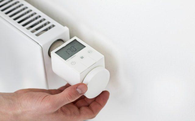 Hand stellt Temperatur am iQ Roomcontrol Heizkörperthermostat ein