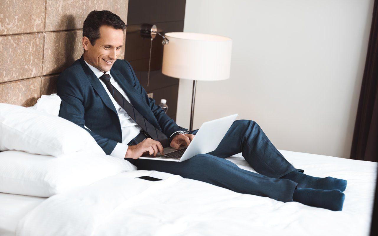 Hotelgast im Businessanzug sitzt auf dem Bett im Hotelzimmer und arbeitet am Laptop