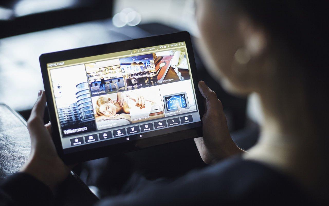 Junge Frau hält im Hotel die digitale Gästemappe iQ Tab hoch