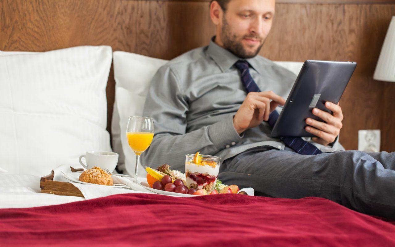 Hotelgast sitzt auf dem Bett im Hotelzimmer mit der digitalen Gästemappe in der Hand und einem bestellten Frühstück neben ihm