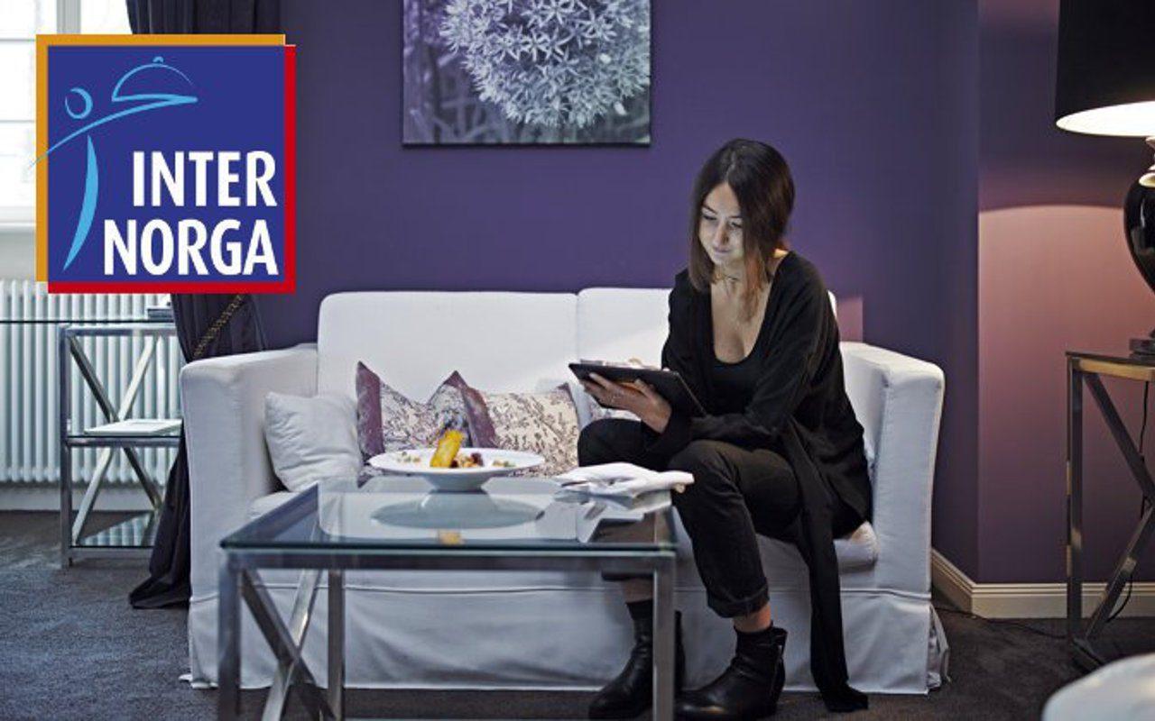 Frau auf Sofa mit digitaler Gästemappe im Hotelzimmer und INTERNORGA - Logo