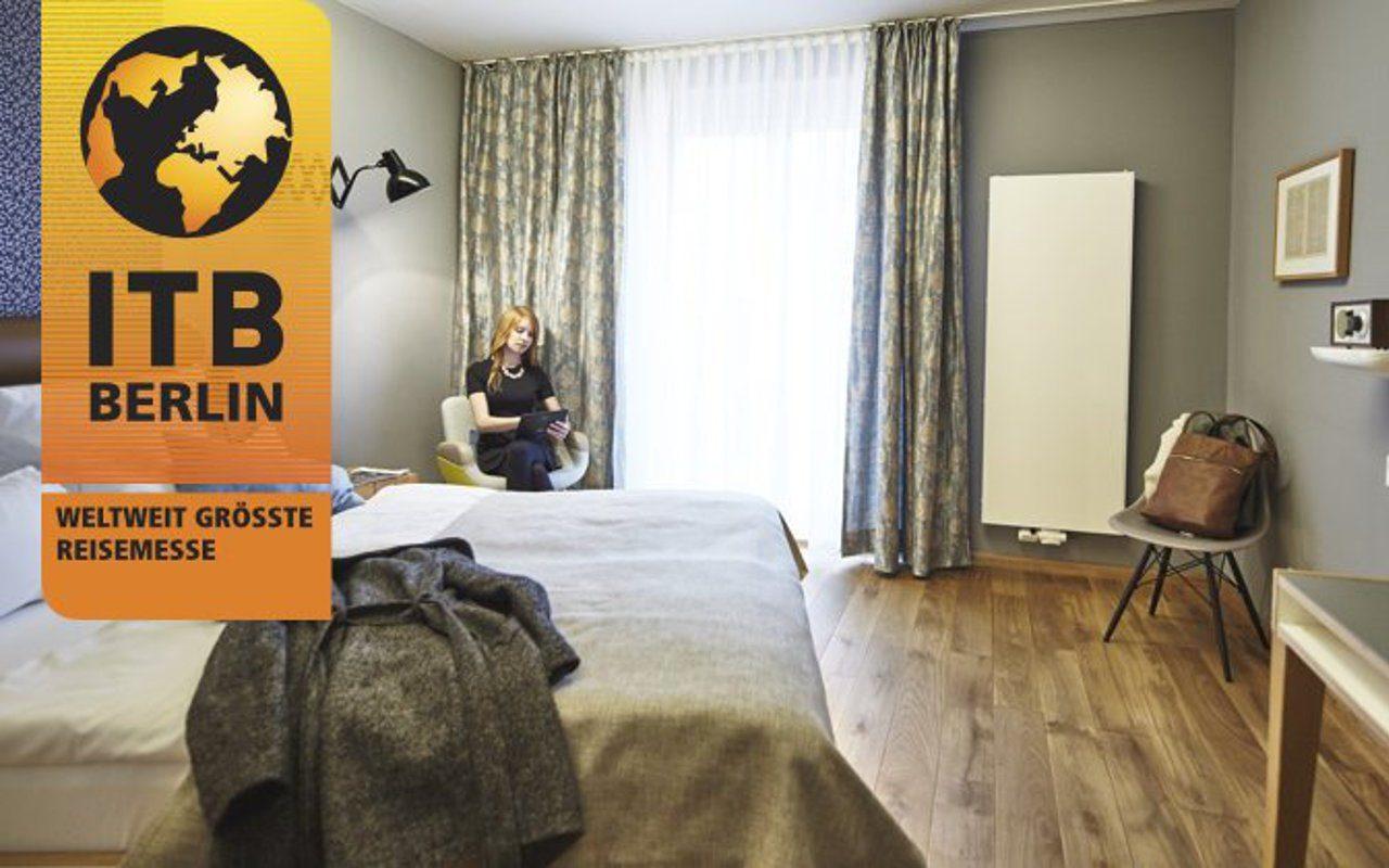 Hotelgast im Hotelzimmer mit digitaler Gästemappe und ITB Logo