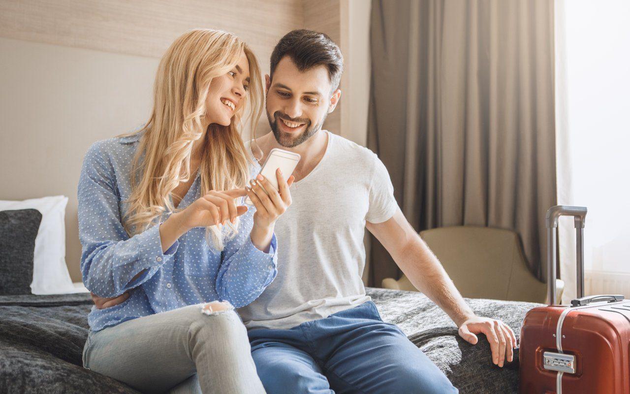 Lächelndes Paar auf dem Bett im Hotelzimmer mit Smartphone in der Hand