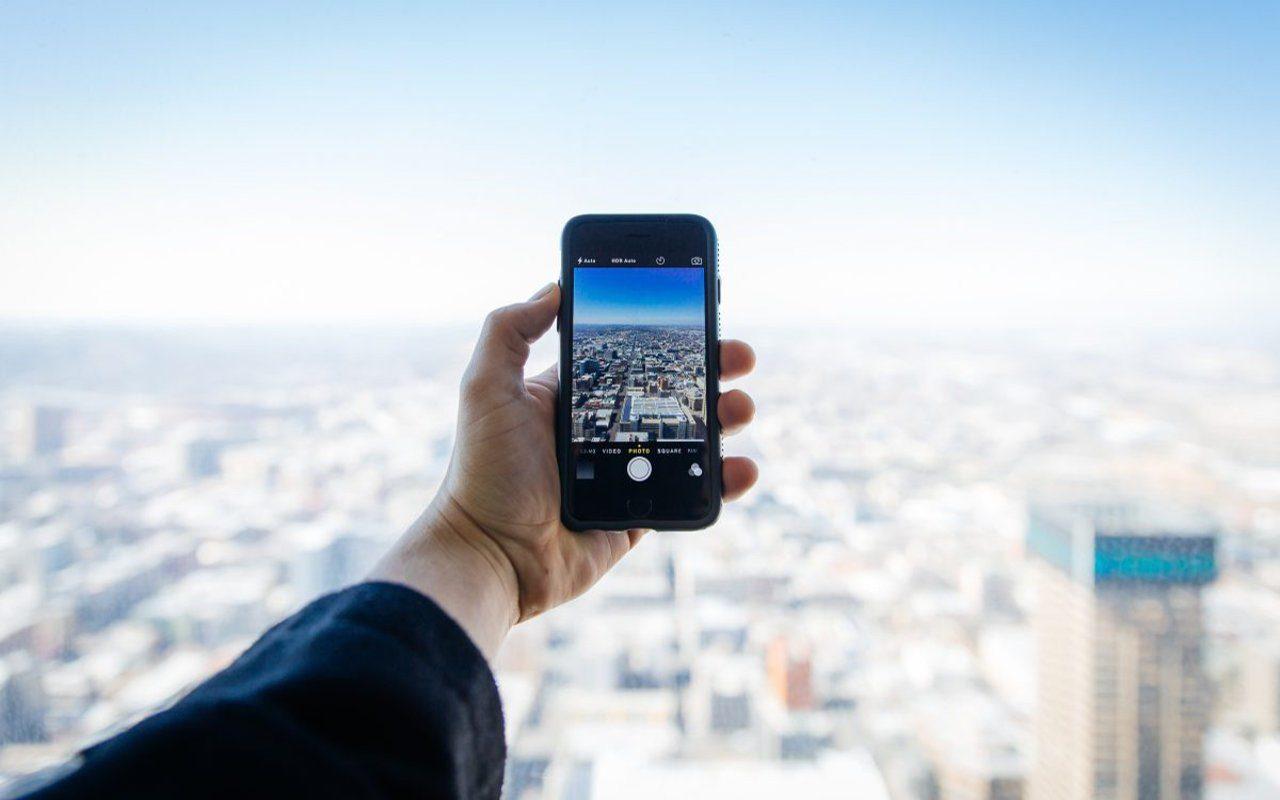 Person fotografiert mit Smartphone vom Dach aus die Stadt