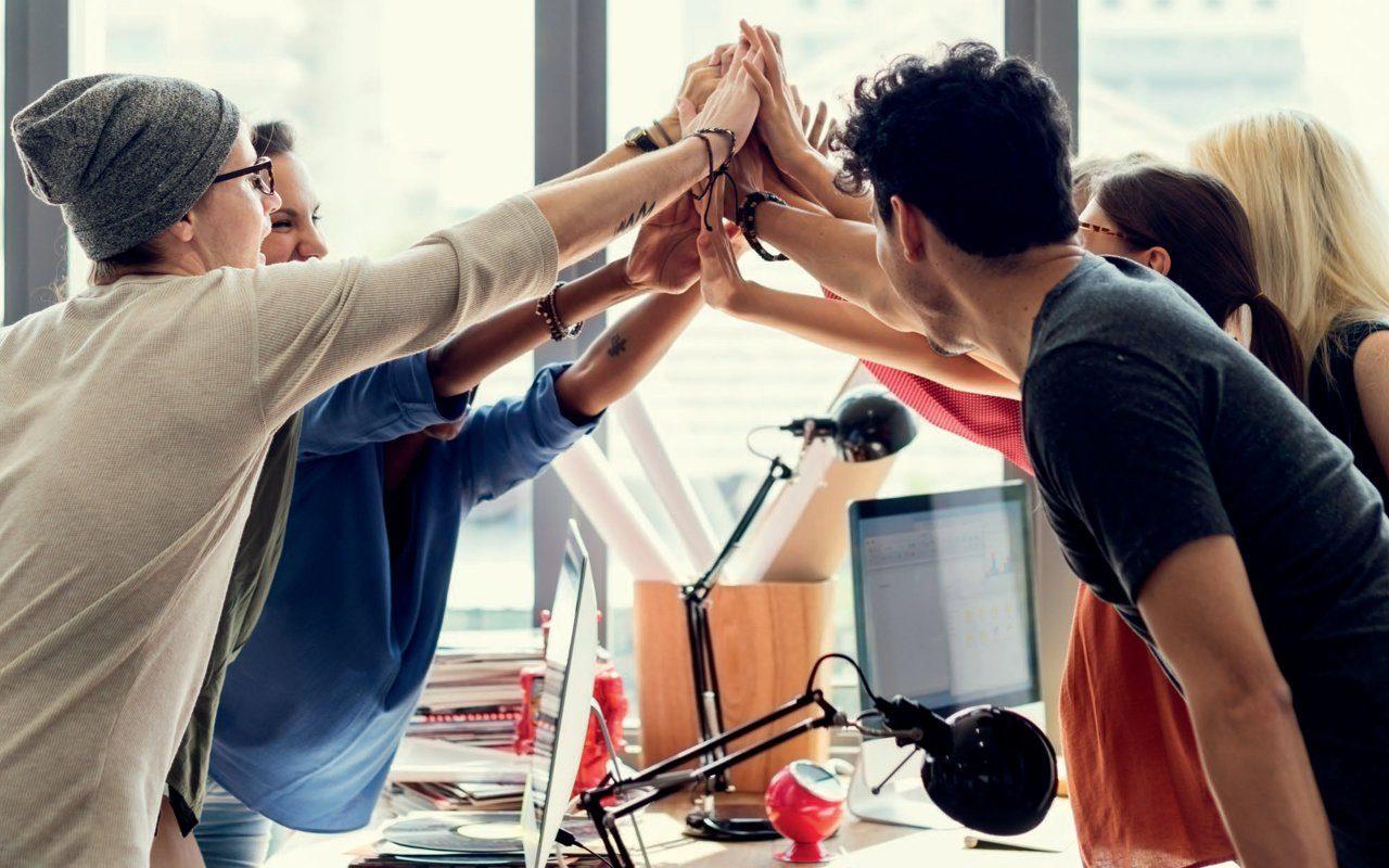 Team von Menschen geben sich um Schreibtisch High five