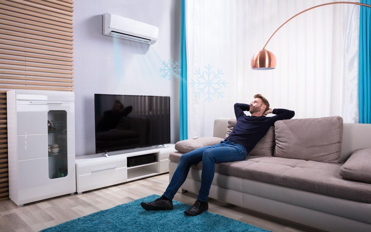 Zufriedener Hotelgast sitzt im Hotelzimmer Klimaanlage läuft