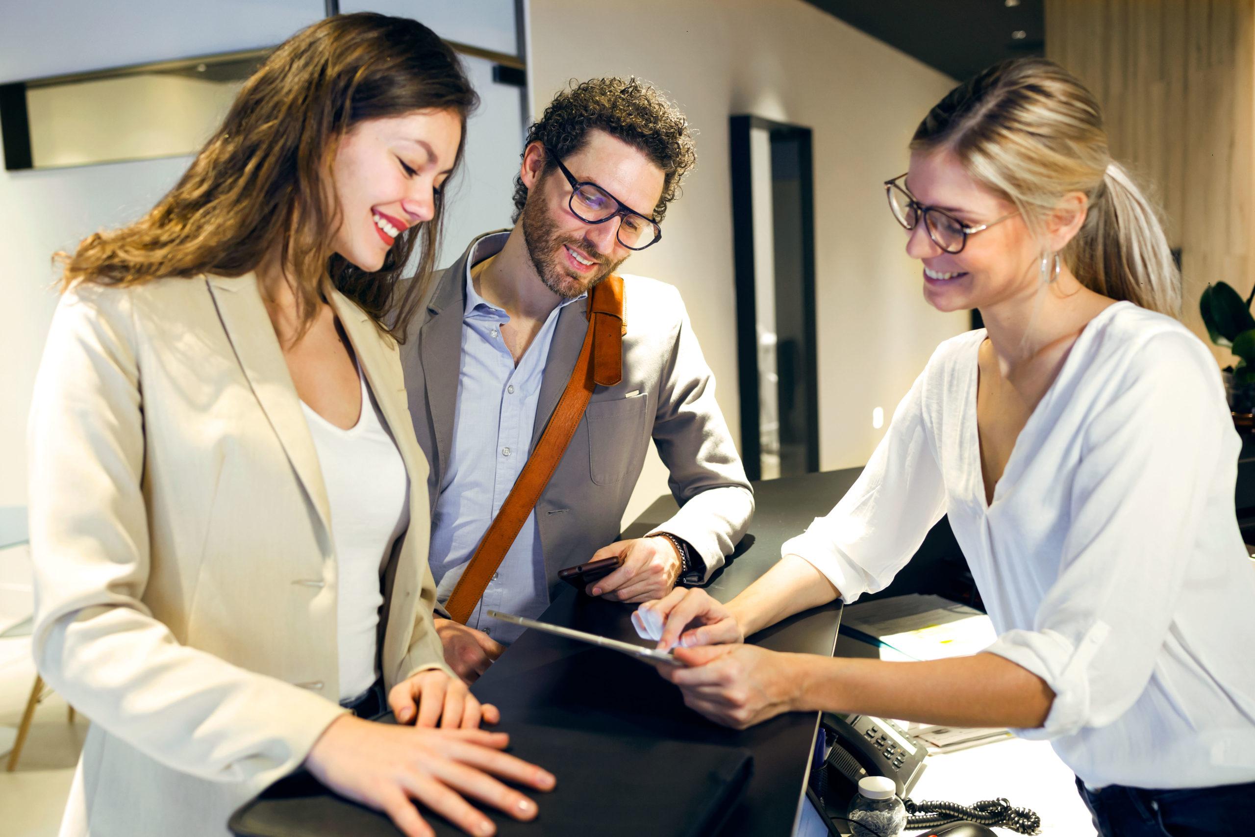 Rezeptionsmitarbeiter und Hotelgäste beim Check-In