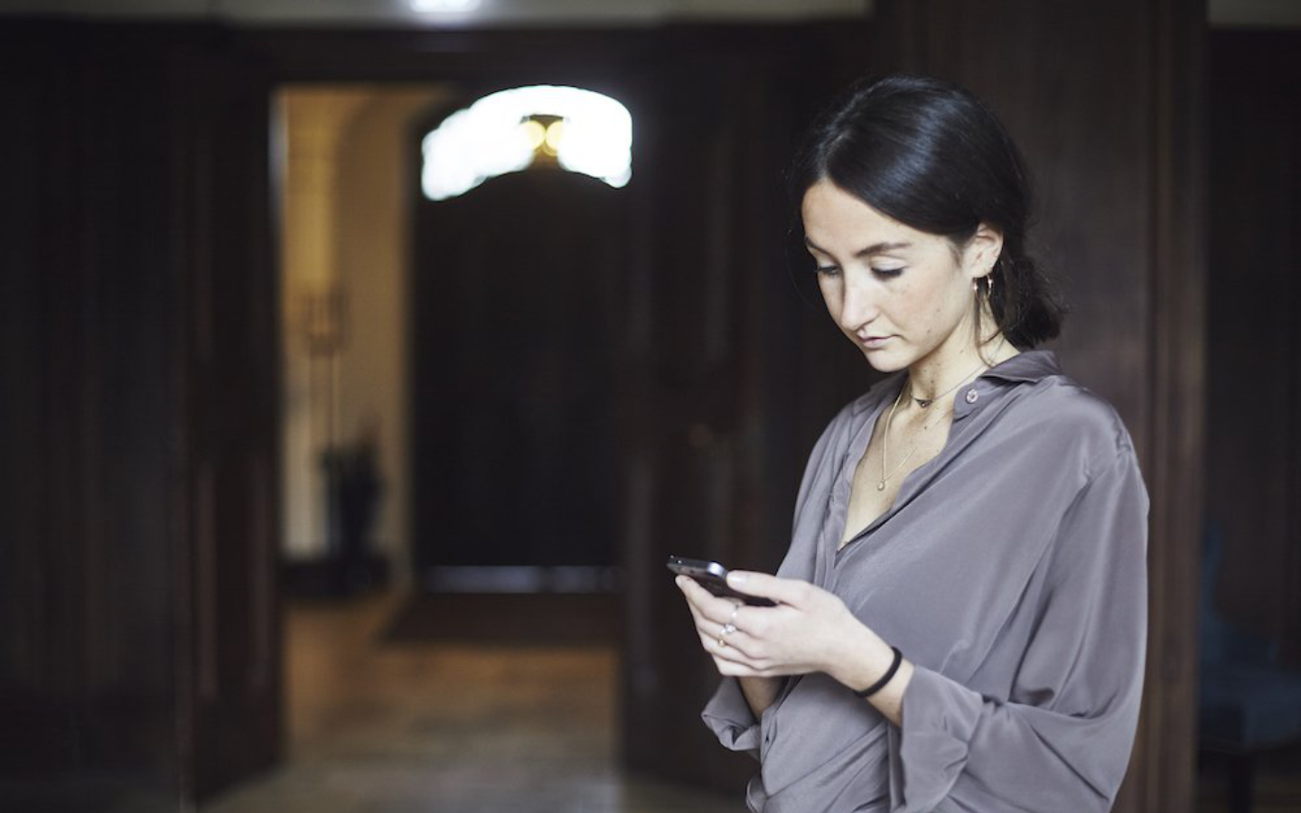 Woman in the hotel corridor with Smartphone